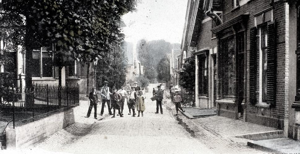 """In het pand rechts had Cornelis Koning zijn bakkerswinkel. Links de ingang van het Postpad., met op de noordhoek de drukkerij""""Het oude postkantoor"""" van G. Wolzak Gzn."""