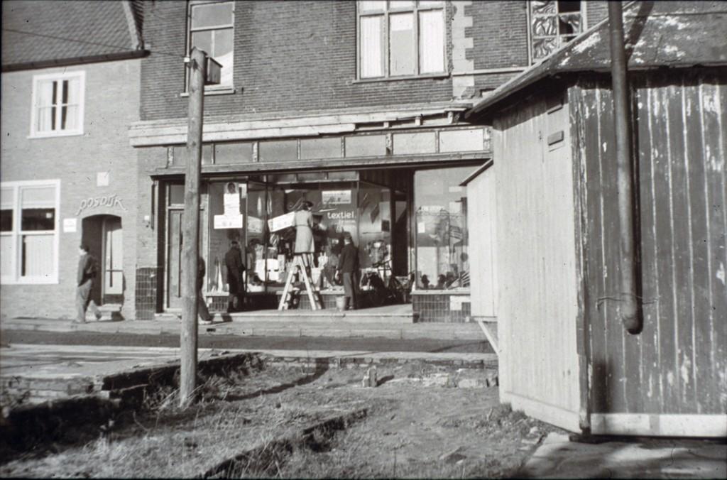 Een van de noodwinkels aan het Plein 1946, nodig om aan winkeliers met verwoeste panden verkoopruimte te verschaffen. Op de achtergrond de winkel van Van der Kraats.