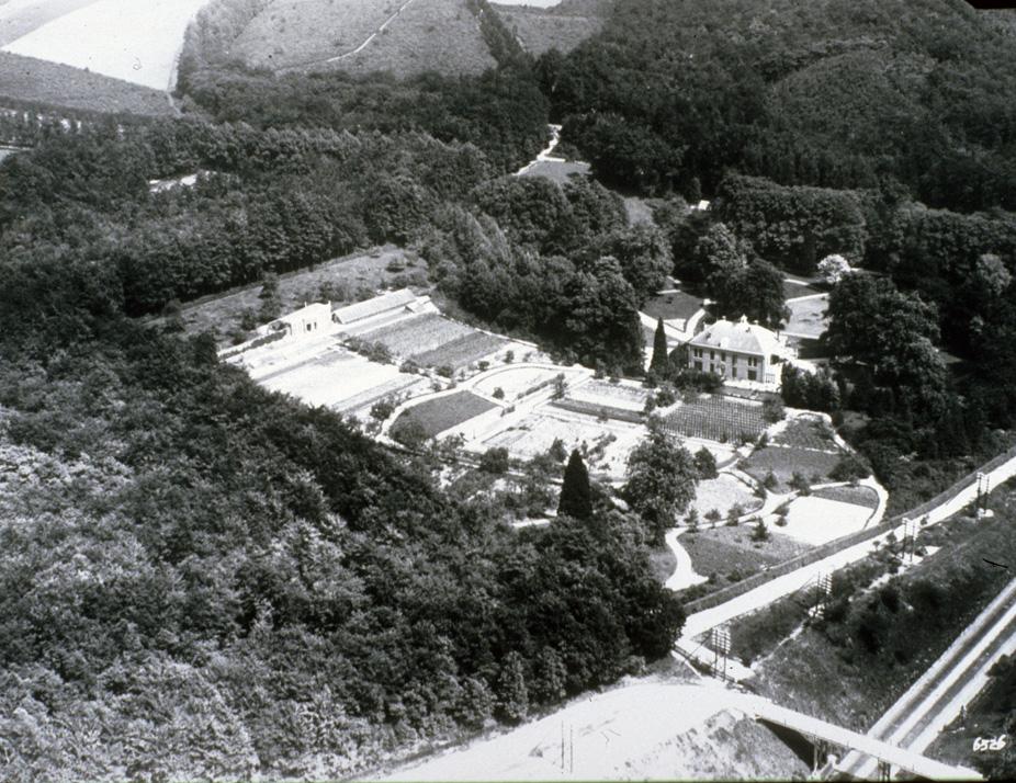 """De parkaanleg rondom het huis """"Mariëndaal"""". Op de voorgrond de achterzijde van het huis met links de oranjerie en rechtsonder de spoorbrug op de Schelmseweg. Bij de bouw van het laboratorium achter het huis ging dit deel van de parkaanleg verloren."""