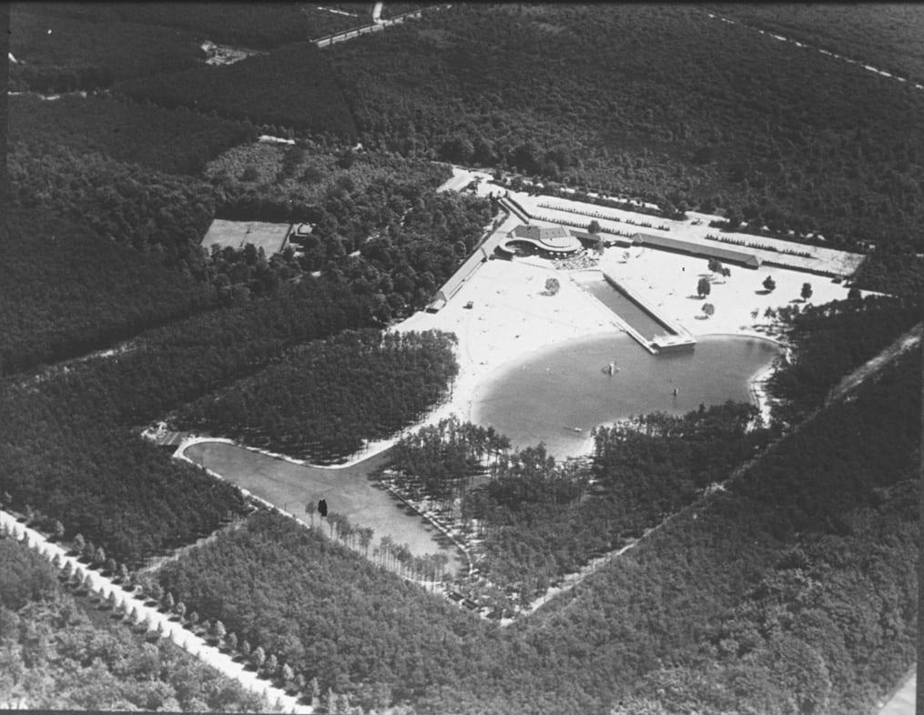 Op de luchtfoto is de indeling van het terrein goed zichtbaar. De kano-/zwemvijver, het golfslagbad en de entree.