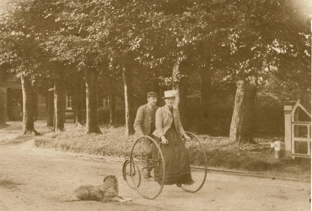 """Ada Wolterbeek met haar echtgenoot op de fiets. Op de achtergrond """"de Koude Herberg""""."""
