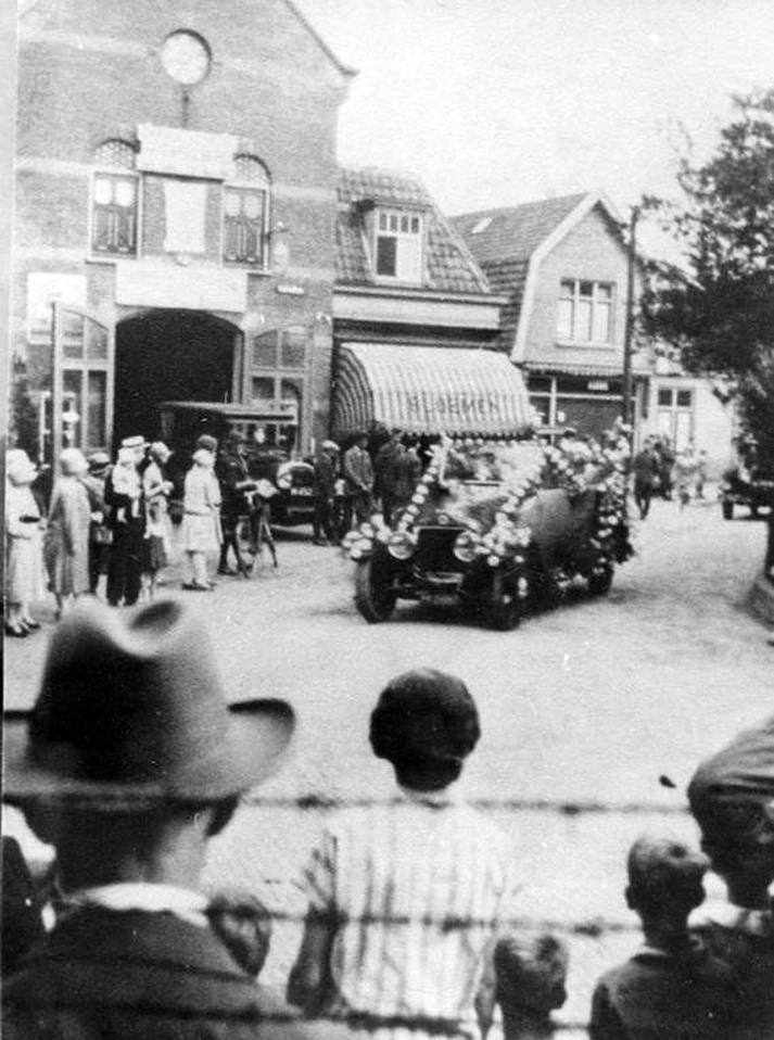 Een optocht van automobielen passeert de garage van W. Sukkel. Rond 1930.
