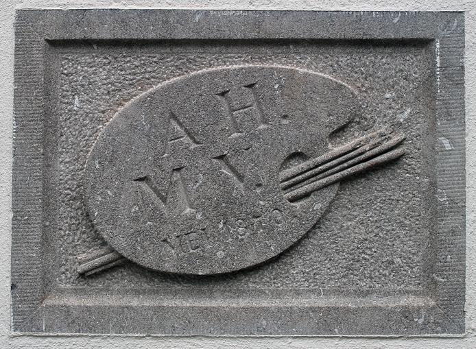 """De gevelsteen van """"Villa Grada"""", in de zuidgevel van het huis op het grote balkon. De initialen van de twee kunstenaars en een palet met penselen sieren de steen."""