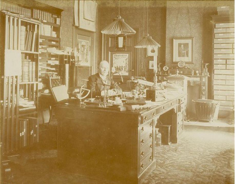 Jacques van Marken aan zijn bureau gezeten.