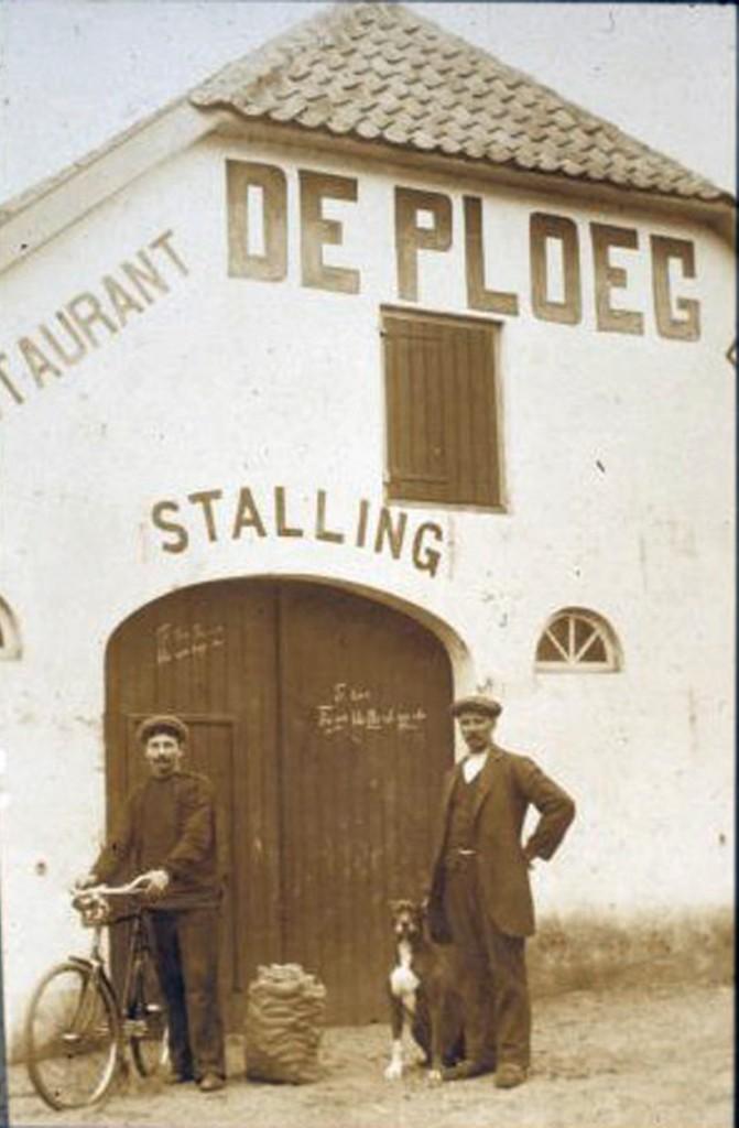 """De stalling van """"de Ploeg"""" met personen op het plaatsje tussen de graanschuur en de stalling."""