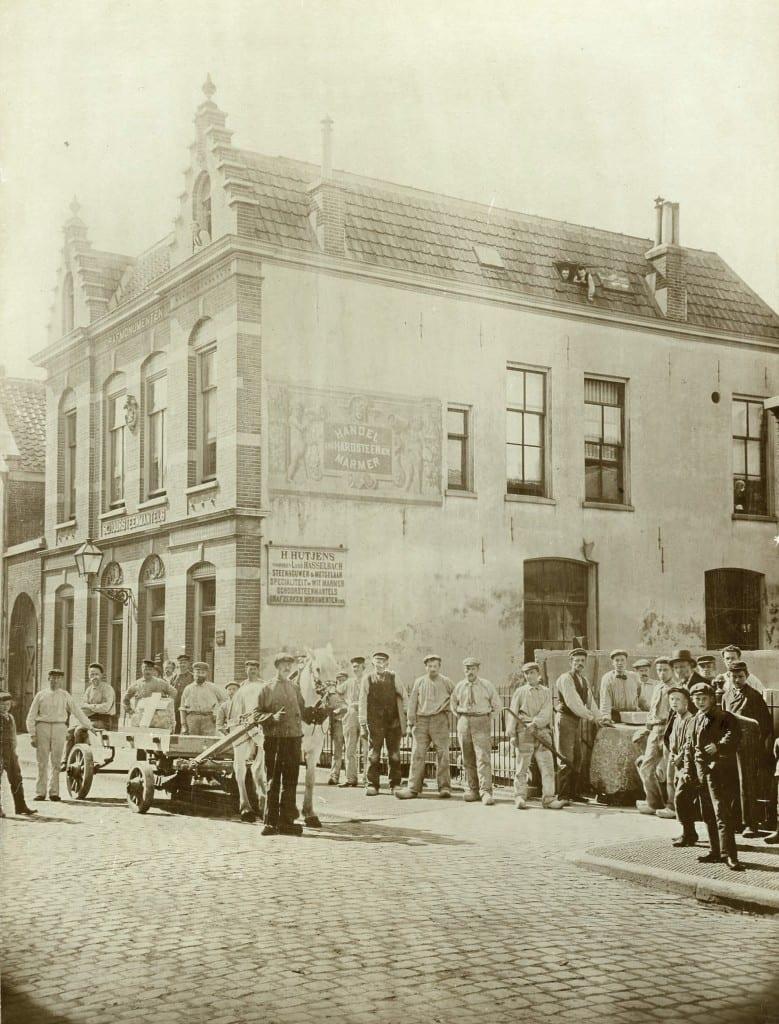 Zicht op de Weerdjesstraat met rechts, voor het pleintje waar de steenhouwerij aan grensde, het personeel van Hutjens. Op de muur links prijst Hutjens zijn bedrijf aan.