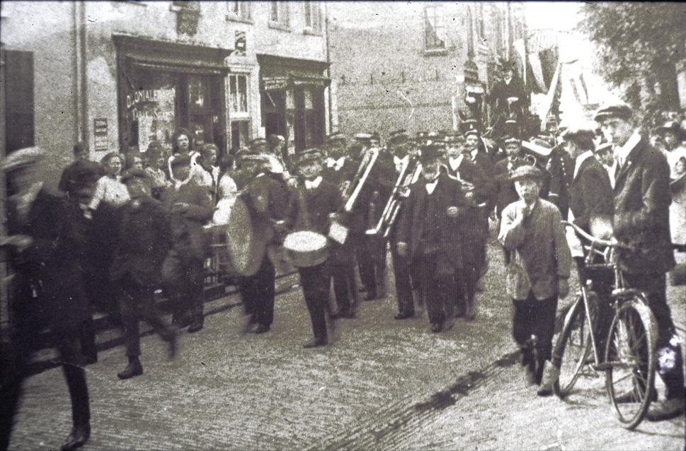 """Evert de Graaf, rechts met hoed en baard, temidden van """"De Eenvoud"""". Ze passeren """"de Handwerkwinkel"""", van mej.H. Vlasveld handelend in tricotages, garen- en band, en modeartikelen."""
