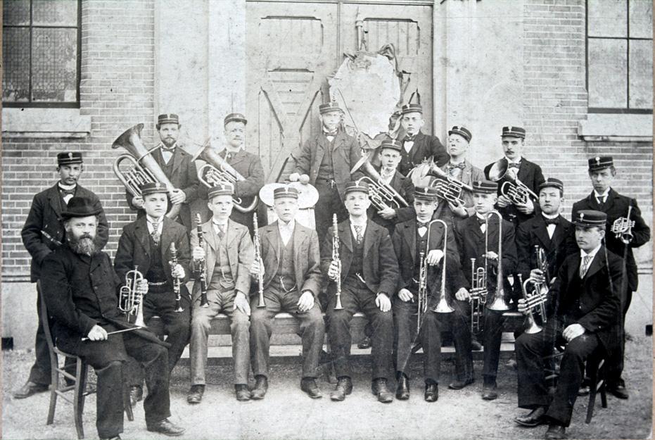 """Harmonie """"De Eenvoud"""" op de stoep van """"Bethanië"""", met zittend links de dirigent Evert de Graaf."""