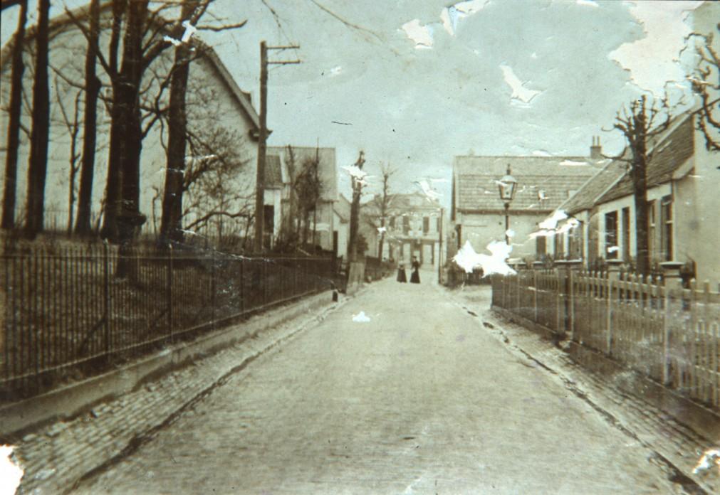 """Weverstraat rond 1900 in noordelijke richting. Links het tuinhek van huis """"Hoogerheide"""". Op de achtergrond het kort daarvoor door T.C. van Rijn betrokken pand, daarvoor enige tijd woonhuis van burgemeester Toulon van der Koog. Ook van Rijn kwam van de Beneden-Weverstraat."""