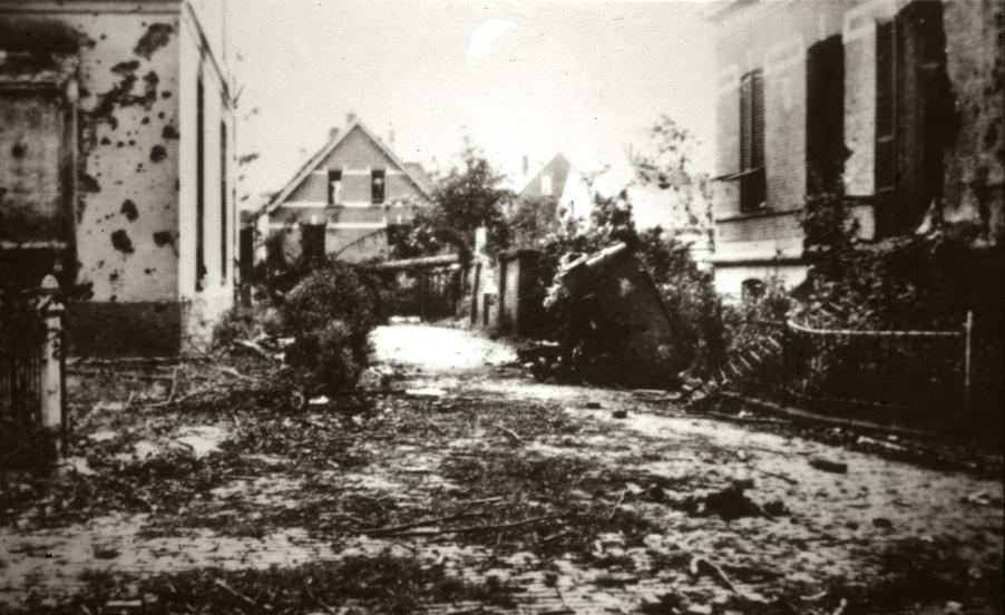 """Zicht vanaf de Weverstraat op de huizen aan de Zuiderbeekweg met achter het linker huis """"""""Vredehof"""" de kop van de Fangmanweg. Foto 1944."""