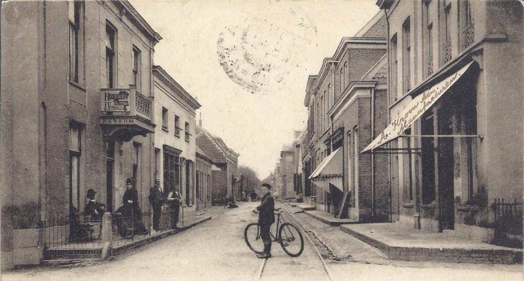 """Dorpsstraat in westelijke richting. Links het """"Hotel Verwaaijen"""". Daarvoor de winkel van de weduwe vrouw Van Vliet (1878). Deze verkocht hier hout en turf. Dan volgde de bakkerij Mekking en het iets terug gebouwde lage pandje van Salomon Cohen (1884), die daar een boter- en kaaswinkeltje had . Voor WOII had Van de Born er een sigarenwinkel."""