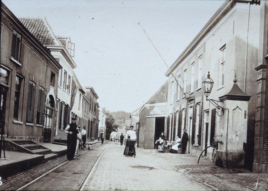 """Rechts, achter de dorpspomp, hotel """"De Reizende Man"""" met de postschuur. Op de achtergrond de kruising Dorpsstraat/ Kerkstraat/Veerweg."""