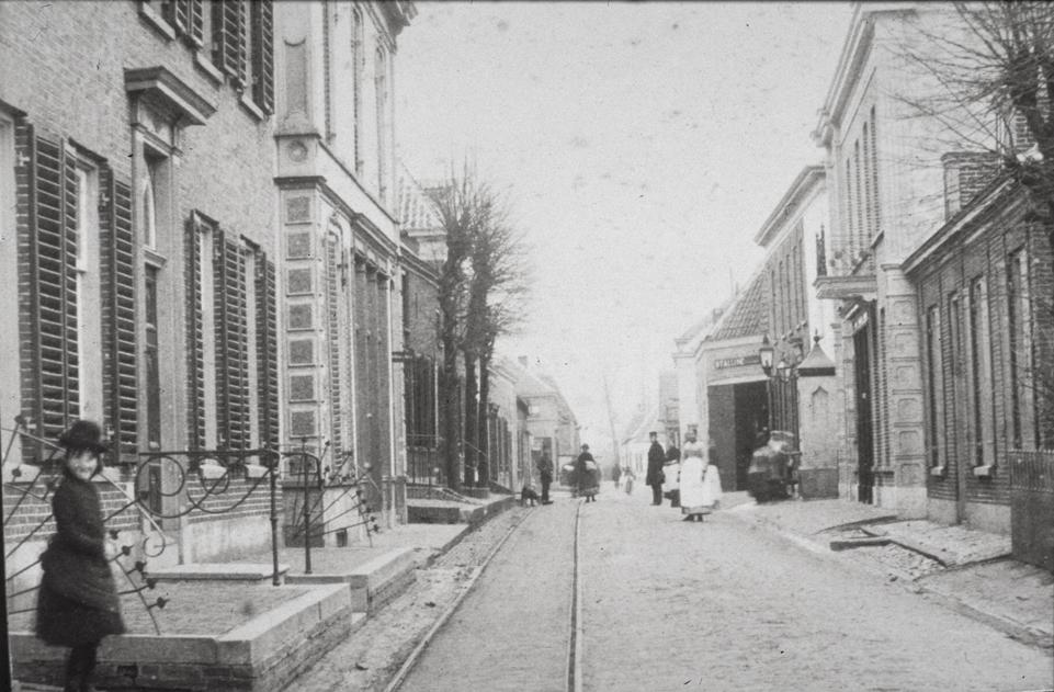 Aan de linkerkant, tussen het gebogen hekwerk, de Kostschool. Daarachter de schoenmakerij van Van Beukeren. Achter de lindebomen staat het boerenhuis van de fam. Schut.