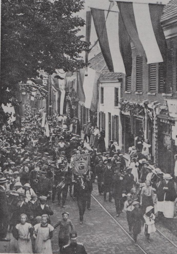 Het Renkums Fanfarecorps passseert, in 1913, rechts de voormalige kostschool voor jonge dames met daarvoor de kruidenierswinkel van Van der Helm.