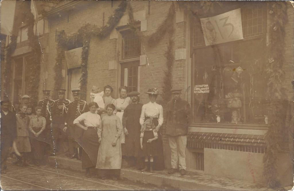 De winkel van J. Schaafsma in 1913. De zadelmaker/ rijtuigbekleder (met platte pet) staat derde van rechts. Links de kruidenierswinkel van zijn echtgenote.
