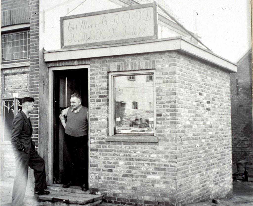 H. Mekking in gesprek met de winkelier Snoek voor zijn noodwinkel, na WOII. Deze lag op het pleintje voor autorijschool Leeuwis