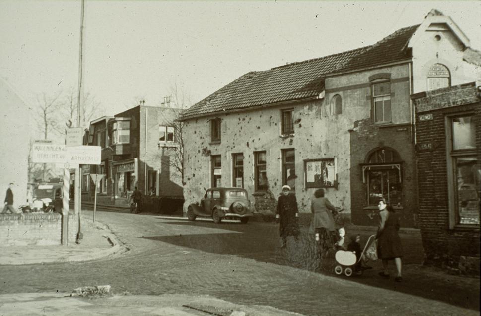 """Kruispunt Dorpsstraat/Kerkstraat/ Veerweg in 1945. Rechts het op de oosthoek met de Kerkstraat gelegen pand. De fotograaf staat met zijn rug naar de puinhopen van """"Hotel Verwaaijen""""."""