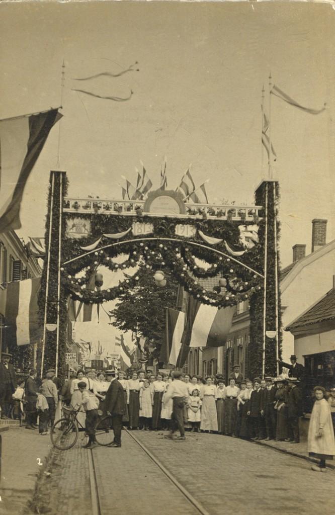 Ereboog ter gelegenheid van 100 jaar Koninkrijk der Nederlanden (1913) met rechts daarachter het pand van Scherrenburg, Dorpsstraat 106.