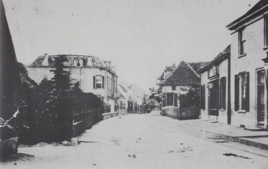 """Zicht op de Dorpsstraat in westelijke richting, voor 1890. Links villa """"Rijnzicht"""" en rechts op de achtergrond de woning van zadelmaker Schaafsma. Daarvoor de winkel van bakker Buddingh met geheel rechts de westelijke helft van het dubbele pand van schoenmaker Van Zwam. Hotel """"Remmerde"""" moest nog worden gebouwd. Ook het pand van de loodgieter Theunissen is nog niet te zien. Na de bouw ervan ontstond tussen het pand van Theunissen en bakker Buddingh een steegje naar de Achterdorpsstraat dat het """"steegje van Buddingh"""" werd genoemd."""
