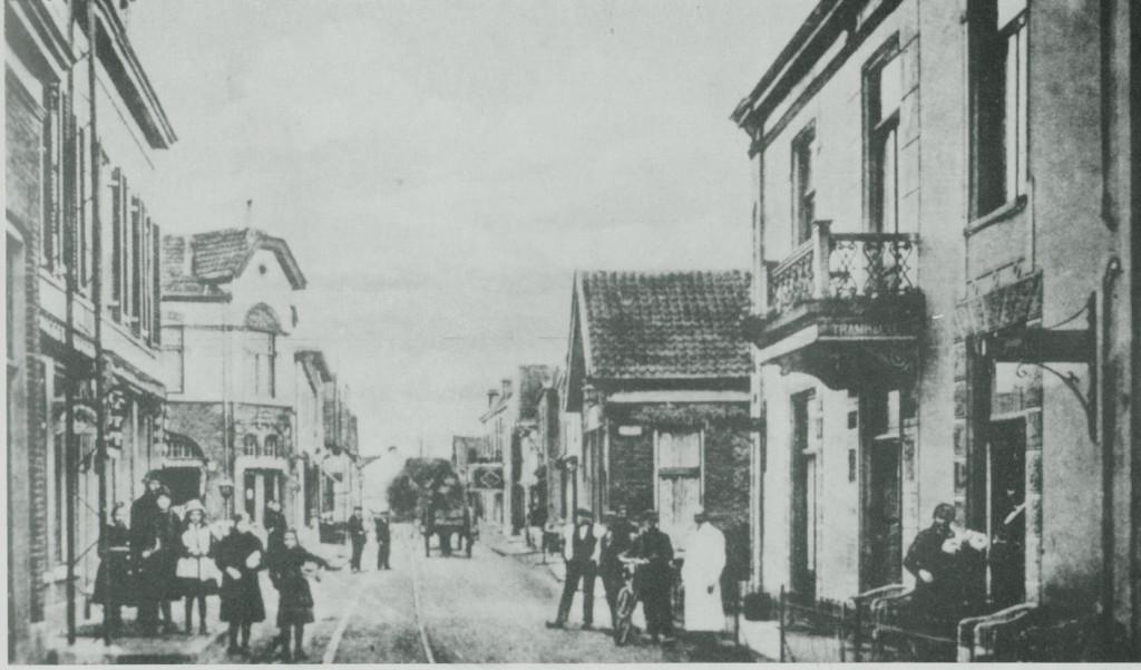 """De Dorpsstraat, gezien in oostelijke richting, met aan de rechterkant """"Hotel Verwaaijen"""" met balkon. Achter het hekje het smalle terras van het hotel. De wachtkamer van de Ooster Stoomtram Maatschappij was in het hotel ondergebracht."""