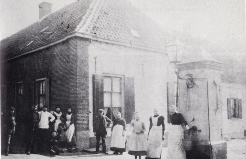 De dorpspomp op de oosthoek van het rijtje met 5 huizen, nabij het voorerf van Van Riessen. Tweede van links de veldwachter Willem den Otter.