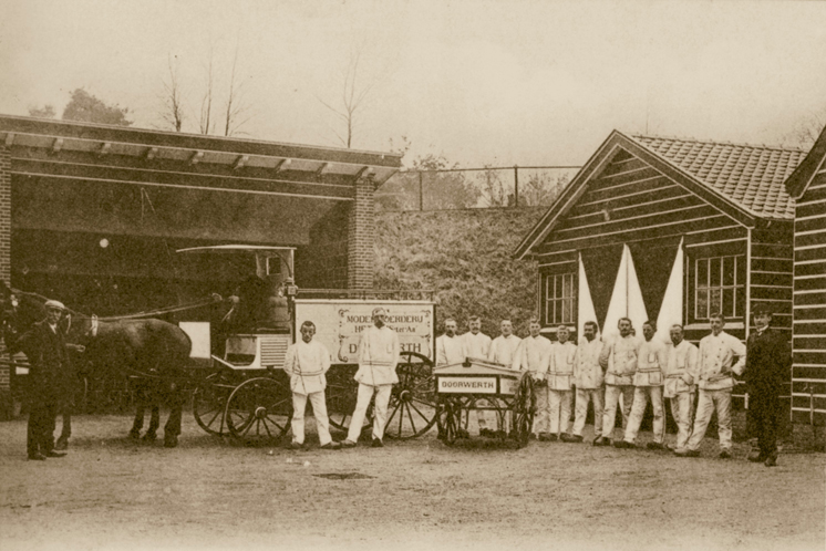 Scheffer, rechts, temidden van zijn personeel op de modelboerderij in het Gat ter Aa (het latere Heveadorp).